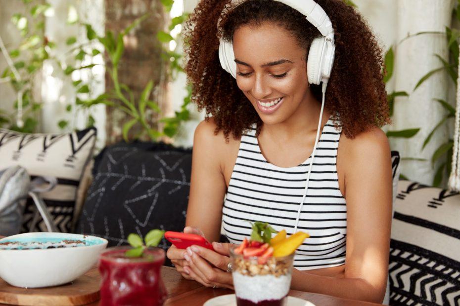 Nainen kuuntelee kuulokkeilla äänikirjaa