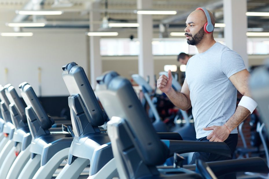 Mies juoksee juoksumatolla kuntosalilla ja kuuntelee musiikkia